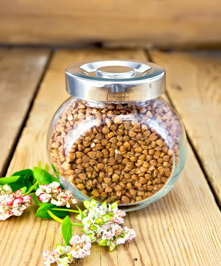 Buckwheat in glass jar and flower on board royalty free stock image