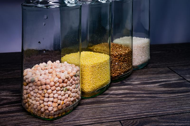 Buckwheat grain, millet, peas and rice in glass jars. royalty free stock photos