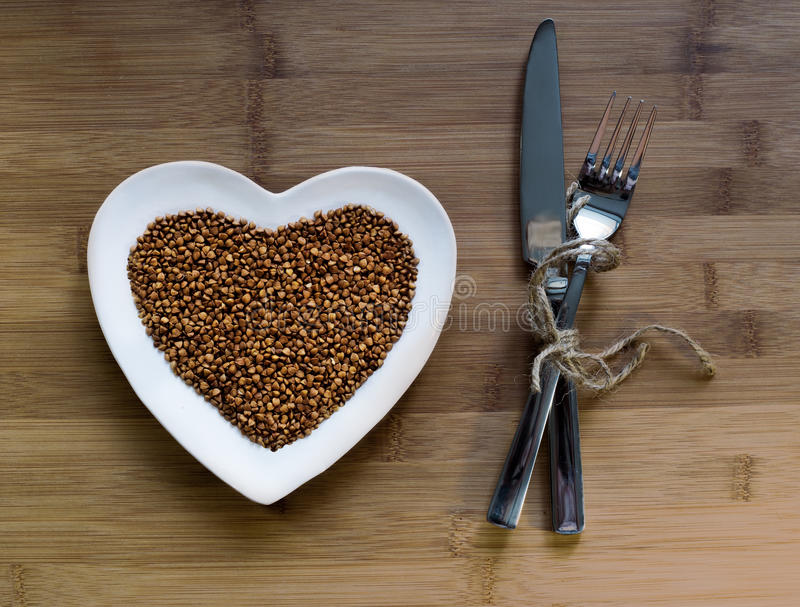 Buckwheat on heart-shaped plate royalty free stock photos