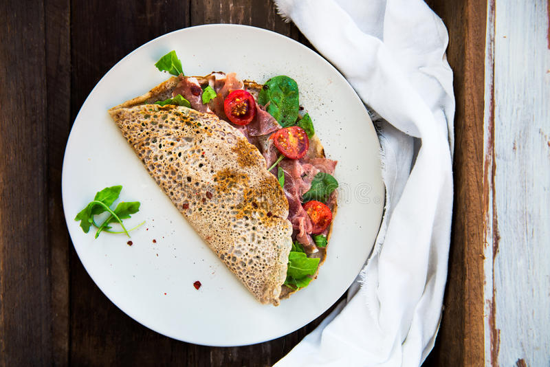 Buckwheat Pancakes with Cherry Tomatoes, Rocket Salad, Spinach, royalty free stock photo
