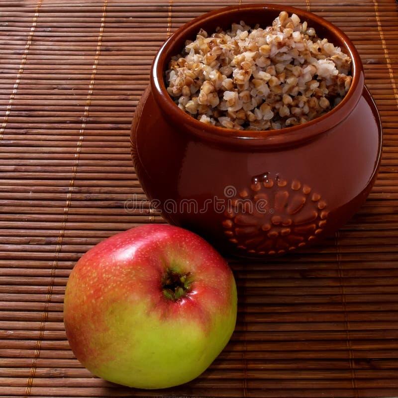 Buckwheat porridge with apple. Buckwheat porridge in the pot with an apple on the table stock photography