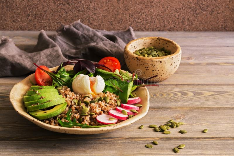 Buckwheat porridge, boiled egg, fresh vegetables on a wooden wood table. Healthy balanced nutrition. Selective focus. Copy space stock images