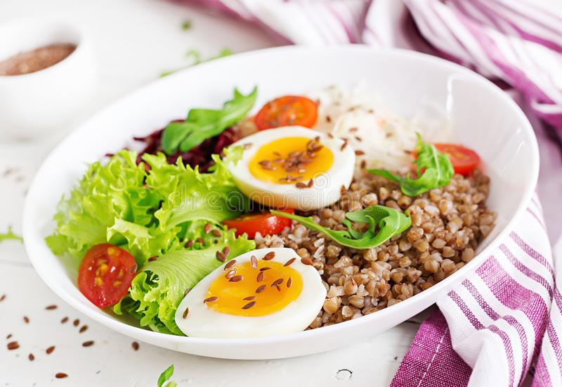 Buckwheat porridge buddha bowls with beetroot, cabbage, boiled eggs. And fresh tomato on white table. Healthy breakfast stock image