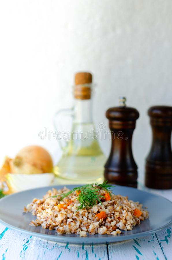 Buckwheat porridge with carrots and dill in a blue plate. On background of Golden onions, green dill and salt and pepper mills stock image