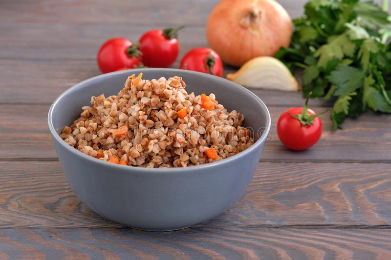 Buckwheat  porridge with carrots and parsley in plate. stock images