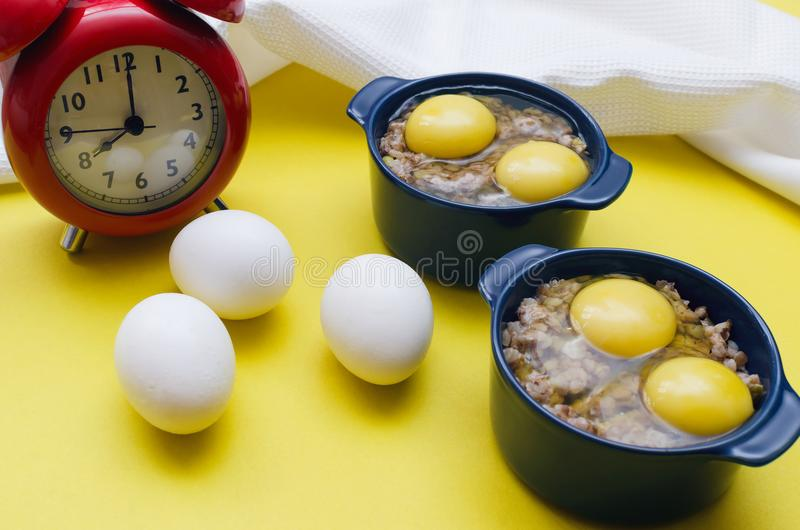 Buckwheat porridge with cheese and egg and red alarm clock. stock photos