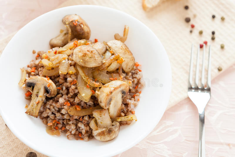 Buckwheat porridge with fried mushrooms royalty free stock photo
