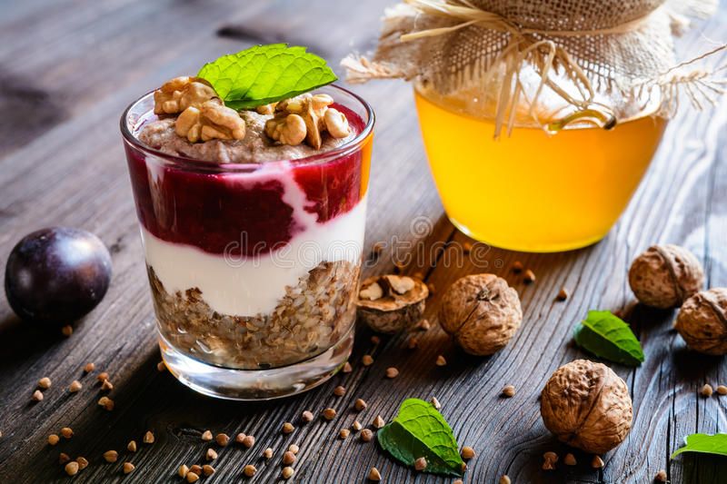 Buckwheat porridge with honey, yoghurt, walnuts and plum puree royalty free stock image