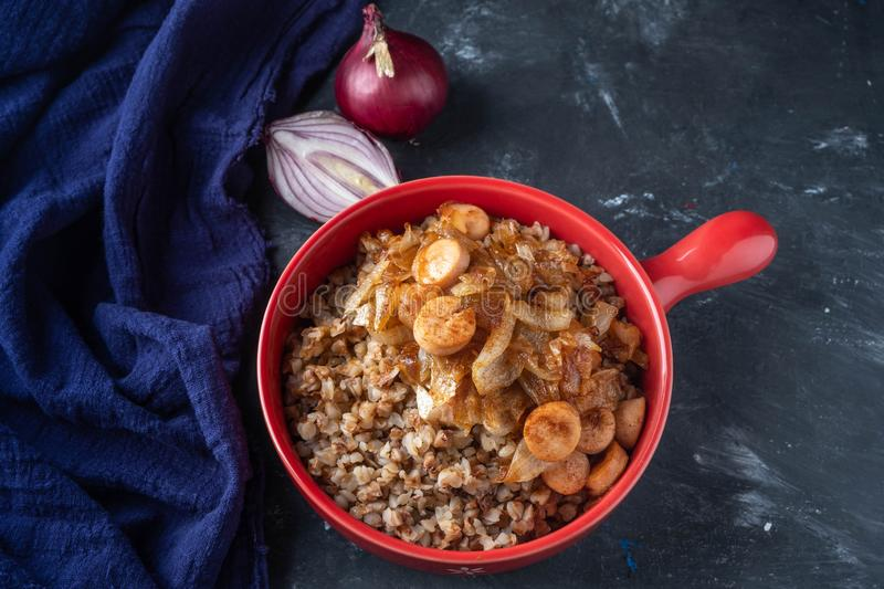 Buckwheat porridge with sausages and fried onions in a red pan on a dark background, copy space stock image