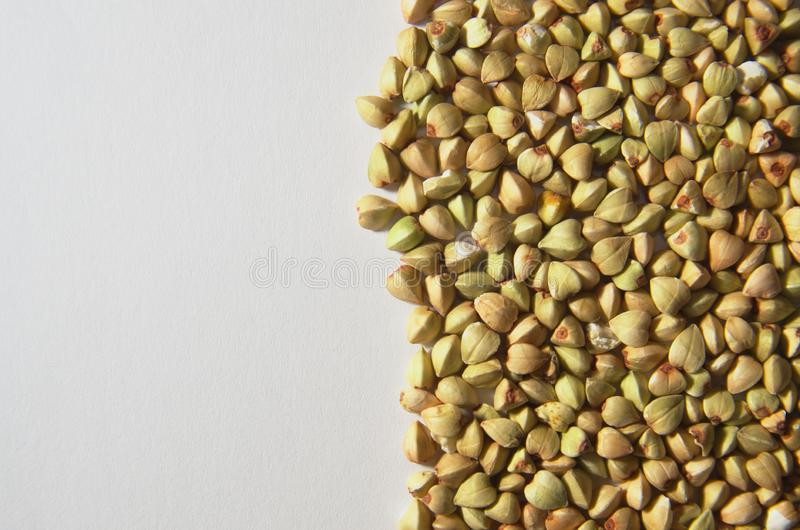Buckwheat seeds on white background. Occupying the right half of the photo. It contains the essential amino acids and, in particular, the amino acid that is royalty free stock image