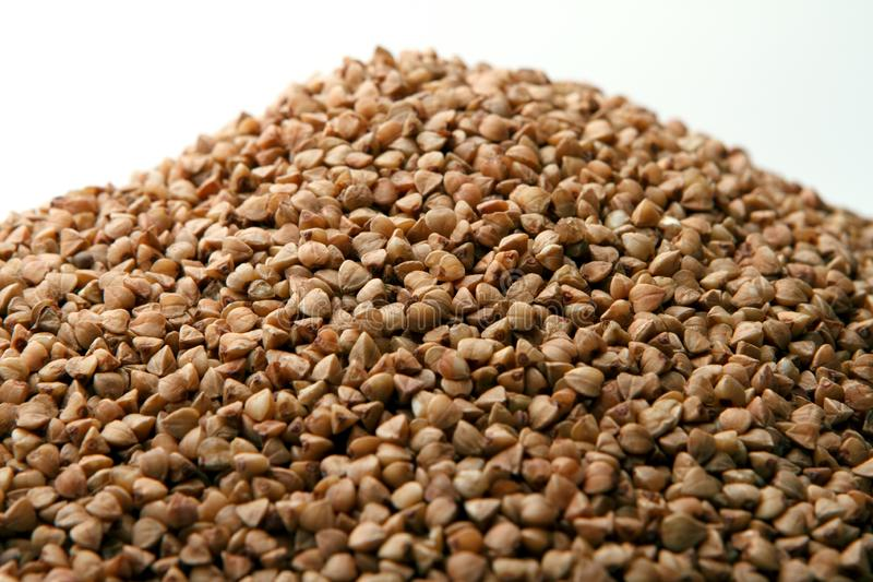 Heap of buckwheat on white background royalty free stock photography