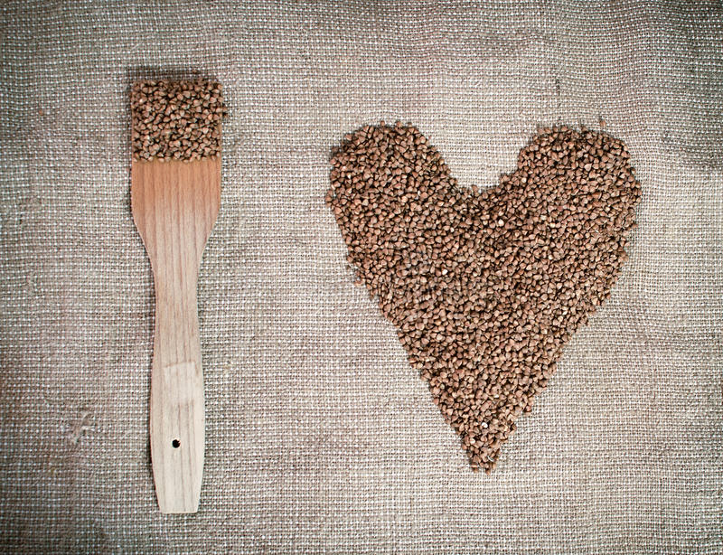 Buckwheat with wooden paddle lying on canvas. Heart shaped. royalty free stock photography