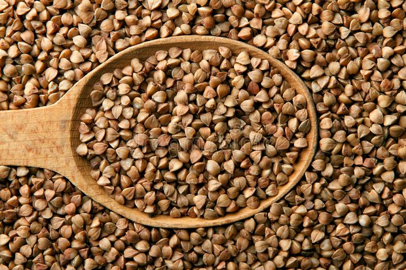 Buckwheat in a wooden spoon royalty free stock image