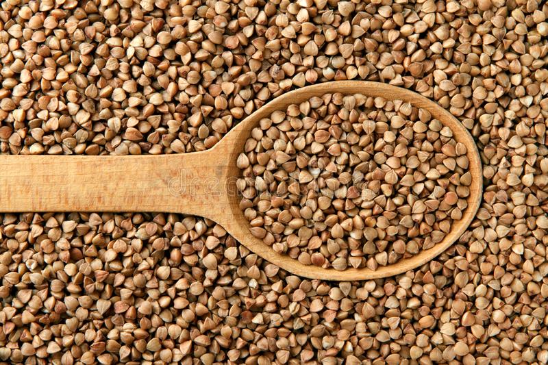 Buckwheat in a wooden spoon royalty free stock photos