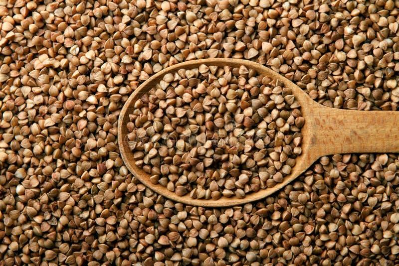 Buckwheat in a wooden spoon stock photos
