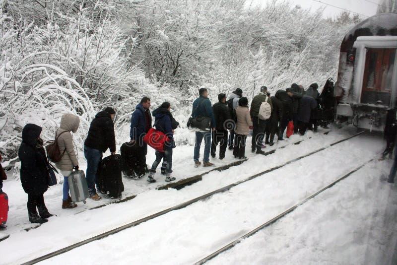 BUCURESTI personer Rumänien-cca 2016 korsar i rad drevstängerna i tung snö med bagage i händer t royaltyfria bilder