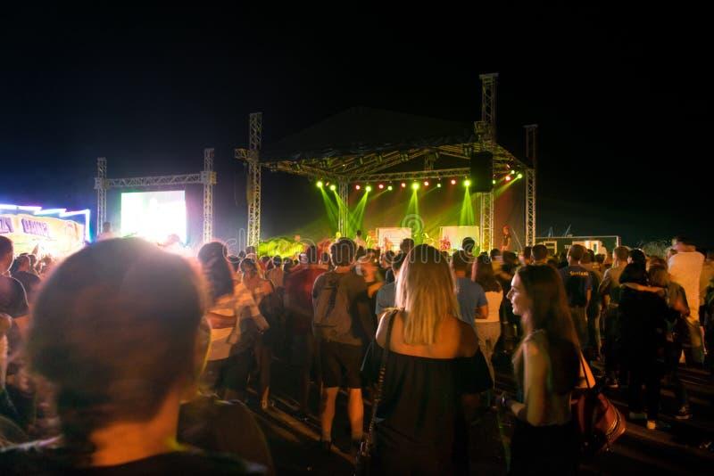 Bucuresti, Romênia Agosto, 01, 2019- Muitos jovens assistindo à noite em um concerto de rock fotos de stock