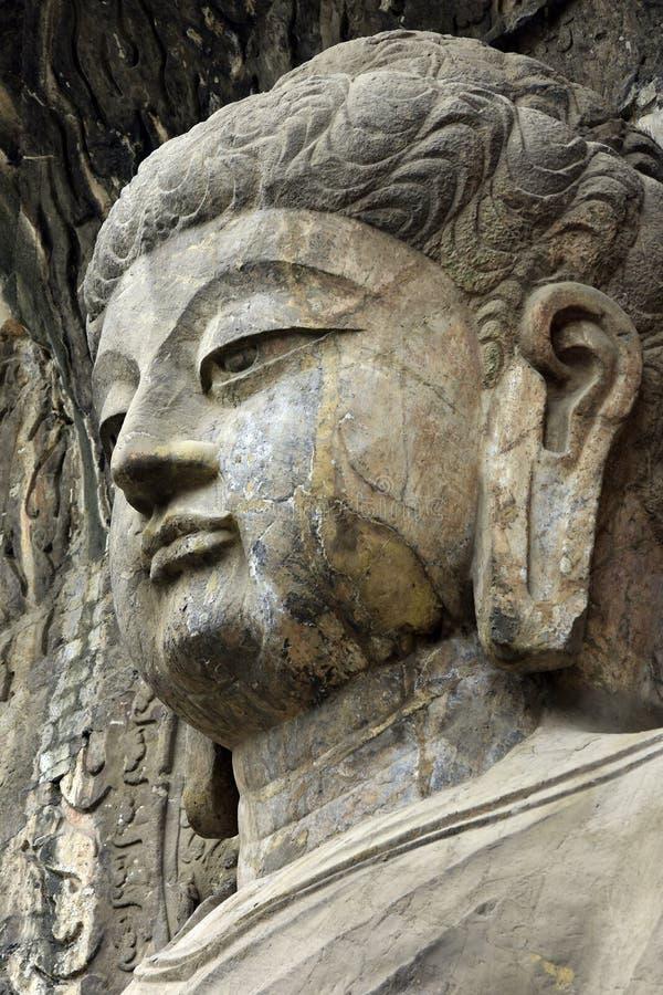 Buda ascendente próxima da cara, estátua velha de pedra de uma Buda no chinês imagem de stock