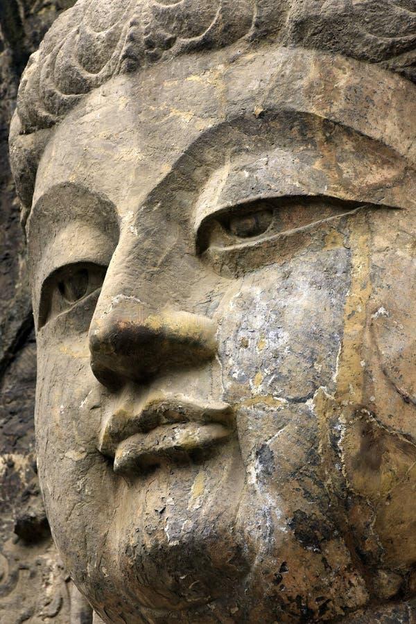 Buda ascendente próxima da cara, estátua velha de pedra de uma Buda no chinês imagem de stock royalty free