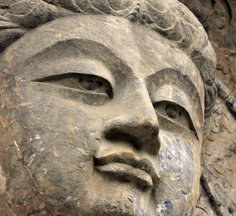 Buda ascendente próxima da cara, estátua velha de pedra de uma Buda no chinês imagens de stock royalty free