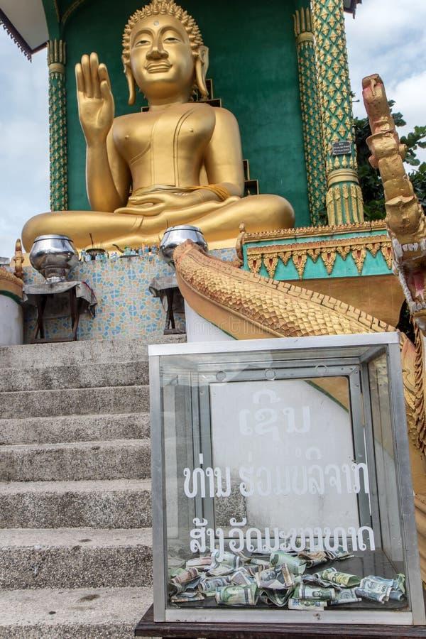 Buda asentado con la caja de dinero para las donaciones, fotografía de archivo