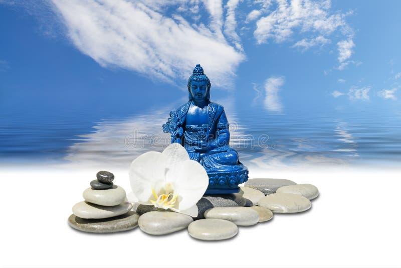 A Buda azul Bhaisajyaguru da medicina, a pedra do zen, as flores brancas da orquídea e o céu refletiram na água imagens de stock royalty free