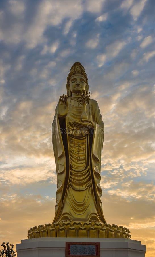 Buda dourada da estátua de Guanyin com fundo crepuscular do céu foto de stock royalty free