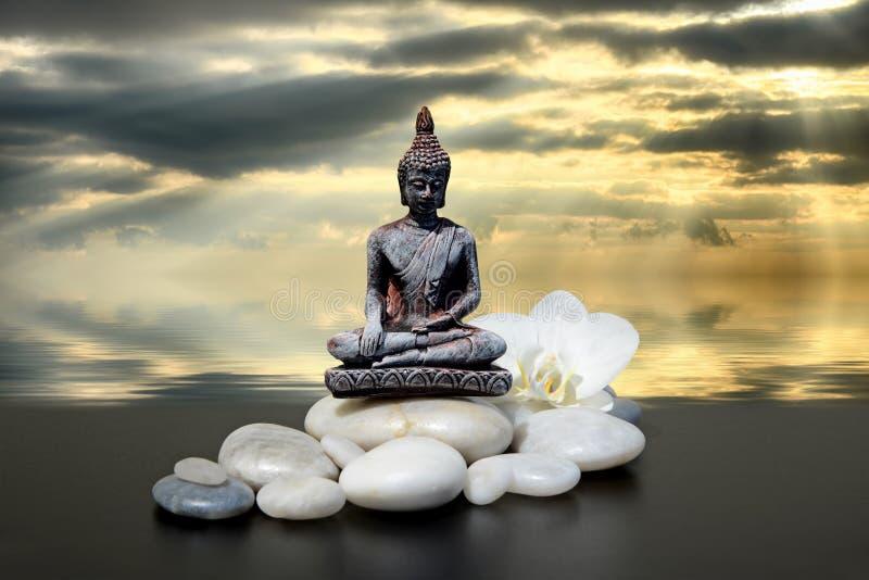 A Buda, a pedra do zen, as flores brancas da orquídea e o céu e as nuvens escuros refletiram na água imagem de stock