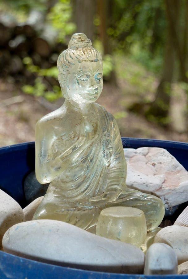 Buda que senta-se em pedras em uma bacia azul imagem de stock