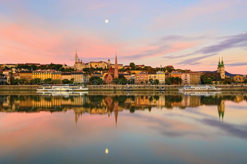Buda side of Budapest city reflecting in still river. Morning view across Danube. Moon royalty free stock images