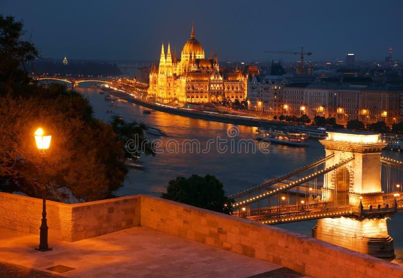 Budapest en la noche - el puente de cadena famoso a través del Danubio y del parlamento húngaro vistos de la colina de Gellert fotos de archivo