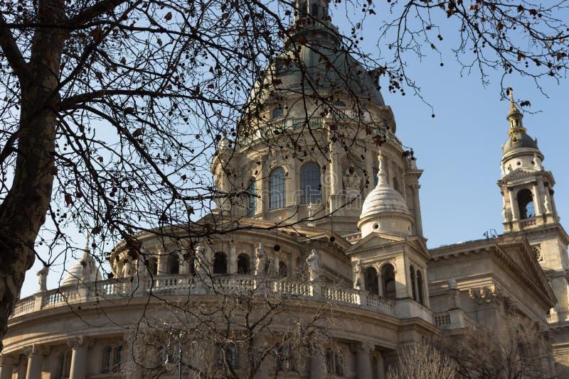 Budapest, Hongrie - 02/19/2018 : Cathédrale du ` s de St Stephen avec le premier plan dénudé d'arbre contre le ciel bleu clair Ar images libres de droits