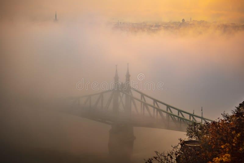 Budapest, Hongrie - lever de soleil brumeux mystérieux avec l'horizon caché et flou de Liberty Bridge Szabadsag de Budapest images stock