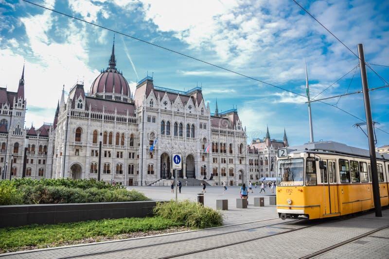 Budapest, Hungagry - 11 settembre, 2018 - passaggi gialli del tram davanti al Parlamento ungherese fotografia stock libera da diritti