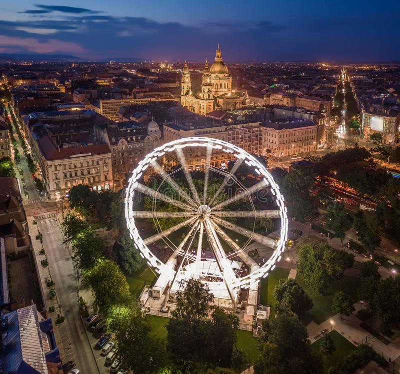 Budapest, Hungary - Aerial drone view of Elisabeth square at blue hour with illuminated ferris wheel and St. Stephen`s Basilica. At background. Summer evening royalty free stock photos