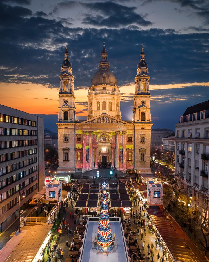 Budapest, Hungary - Aerial drone view of Europe`s most beautiful Christmas market with the illuminated St.Stephen`s Basilica. Ice rink, Christmas tree and stock images