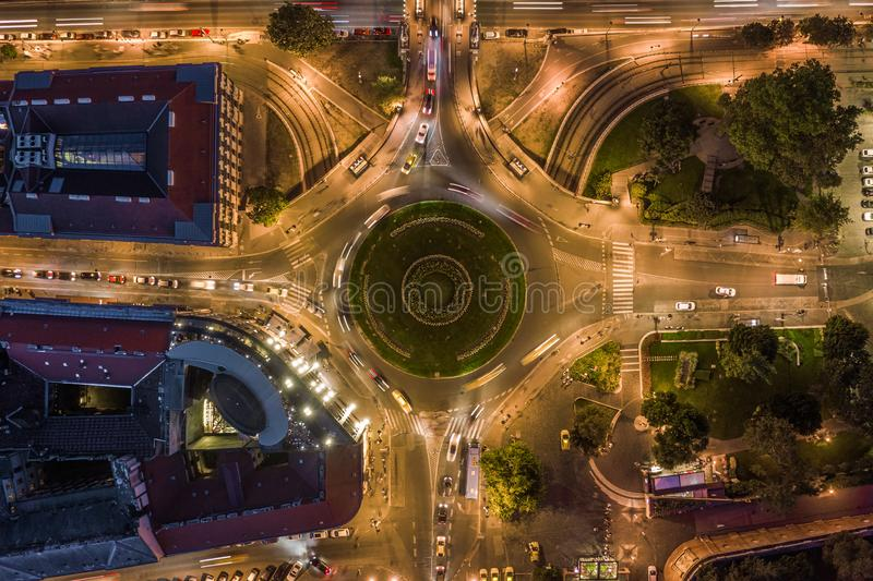 Budapest, Hungary - Aerial drone view of illuminated Clark Adam square roundabout from above at evening with traffic. And light trails stock images