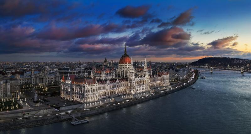Budapest, Hungary - Aerial panoramic view of the beautiful illuminated Parliament of Hungary with Szechenyi Chain Bridge. Statue of Liberty and colurful clouds royalty free stock images