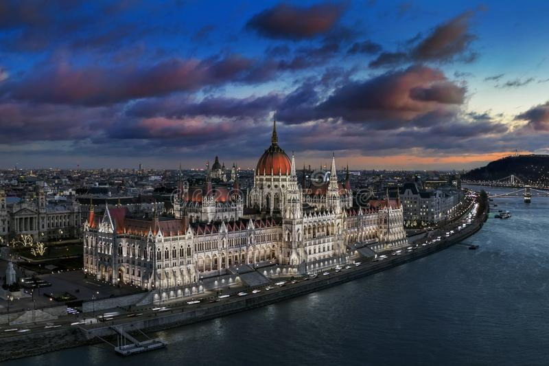 Budapest, Hungary - Aerial panoramic view of the beautiful illuminated Parliament of Hungary with Szechenyi Chain Bridge. Statue of Liberty and colurful clouds stock photo