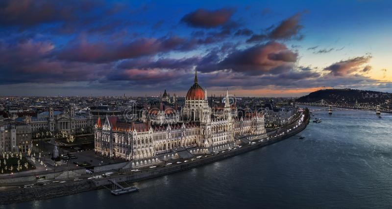 Budapest, Hungary - Aerial panoramic view of the beautiful illuminated Parliament of Hungary with Szechenyi Chain Bridge. Statue of Liberty and colurful clouds stock image