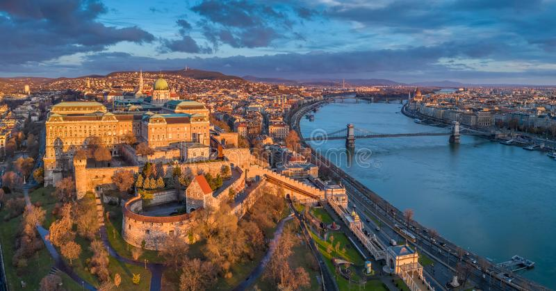 Budapest, Hungary - Aerial panoramic view of Buda Castle Royal Palace with Szechenyi Chain Bridge, Parliament. And colorful clouds at sunrise stock images