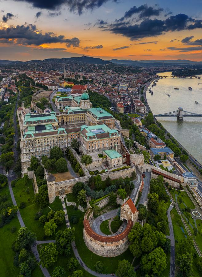 Budapest, Hungary - Aerial skyline view of Buda Castle Royal Palace with Matthias Church, Szechenyi Chain Bridge and Buda Hills. With a beautiful orange sunset royalty free stock images