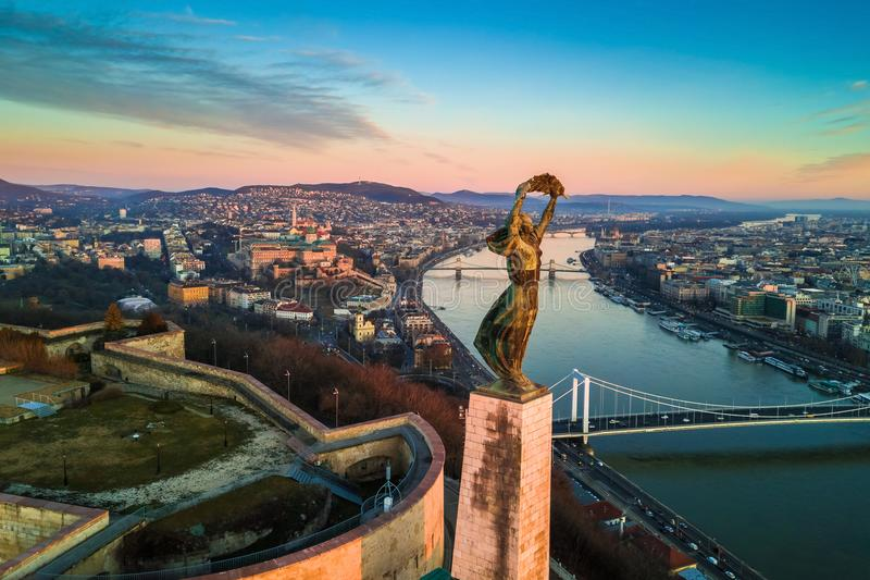 Budapest, Hungary - Aerial skyline view of Statue of Liberty with Buda Castle Royal Palace. And Chain Bridge at background. Morning sunrise with blue sky and royalty free stock photo