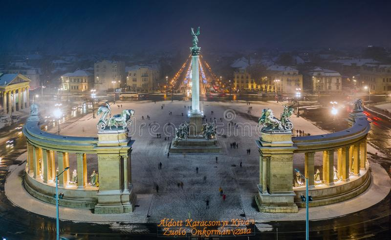 Budapest, Hungary - Aerial view of angel sculpture at Heroes` Square Hosok tere with Christmas decorated Andrassy street. Heavy snowing in Budapest royalty free stock photo