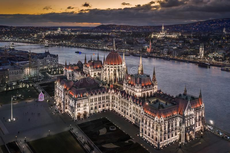 Budapest, Hungary - Aerial view of the beautiful illuminated Parliament of Hungary at dusk with Szechenyi Chain Bridge. Fisherman`s Bastion and other famous stock image