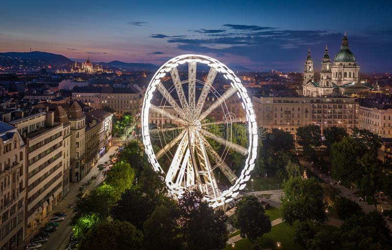 Budapest, Hungary - Aerial view of Elisabeth square at dusk with illuminated ferris wheel, St. Stephen`s Basilica and Parliament. Budapest, Hungary - Aerial view stock photo
