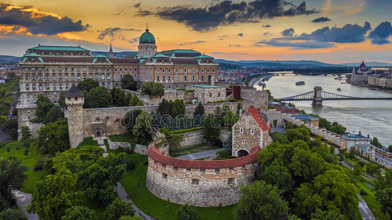 Budapest, Hungary - Aerial view of the famous Buda Castle Royal Palace with Szechenyi Chain Bridge and Hungarian Parliament. Building at sunset time with stock photos