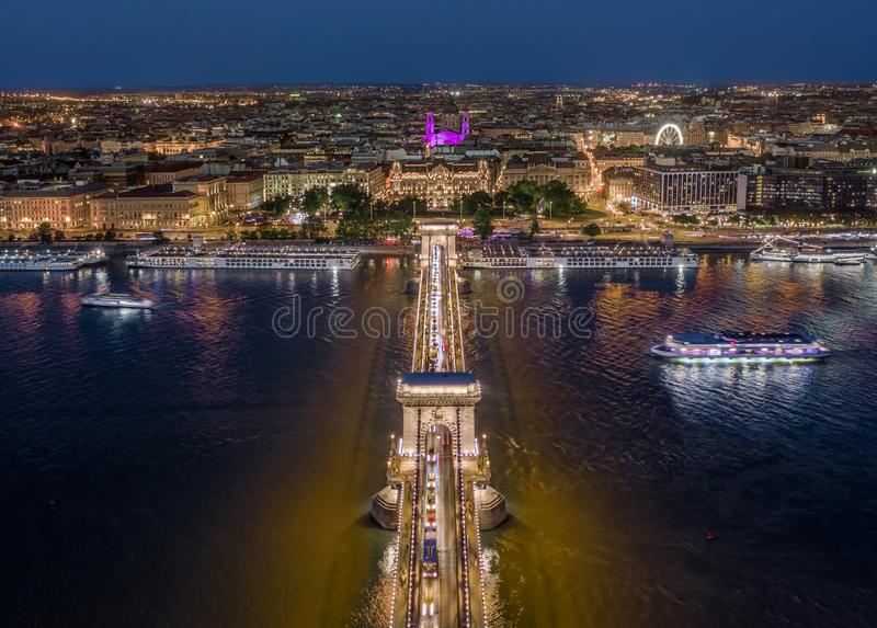 Budapest, Hungary - Aerial view of illuminated Szechenyi Chain Bridge with St. Stephen`s Basilica, ferris wheel and cruise ships. On River Danube at blue hour royalty free stock photos