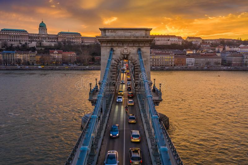 Budapest, Hungary - Aerial view of Szechenyi Chain Bridge with afternoon traffic, beautiful golden sunset sky. Buda Castle Royal Palace and Buda District at stock photography