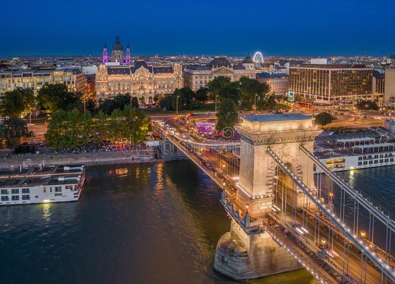 Budapest, Hungary - Aerial view of Szechenyi Chain Bridge with St. Stephen`s Basilica, ferris wheel and cruise ships at blue hour. On a nice summer evening royalty free stock images